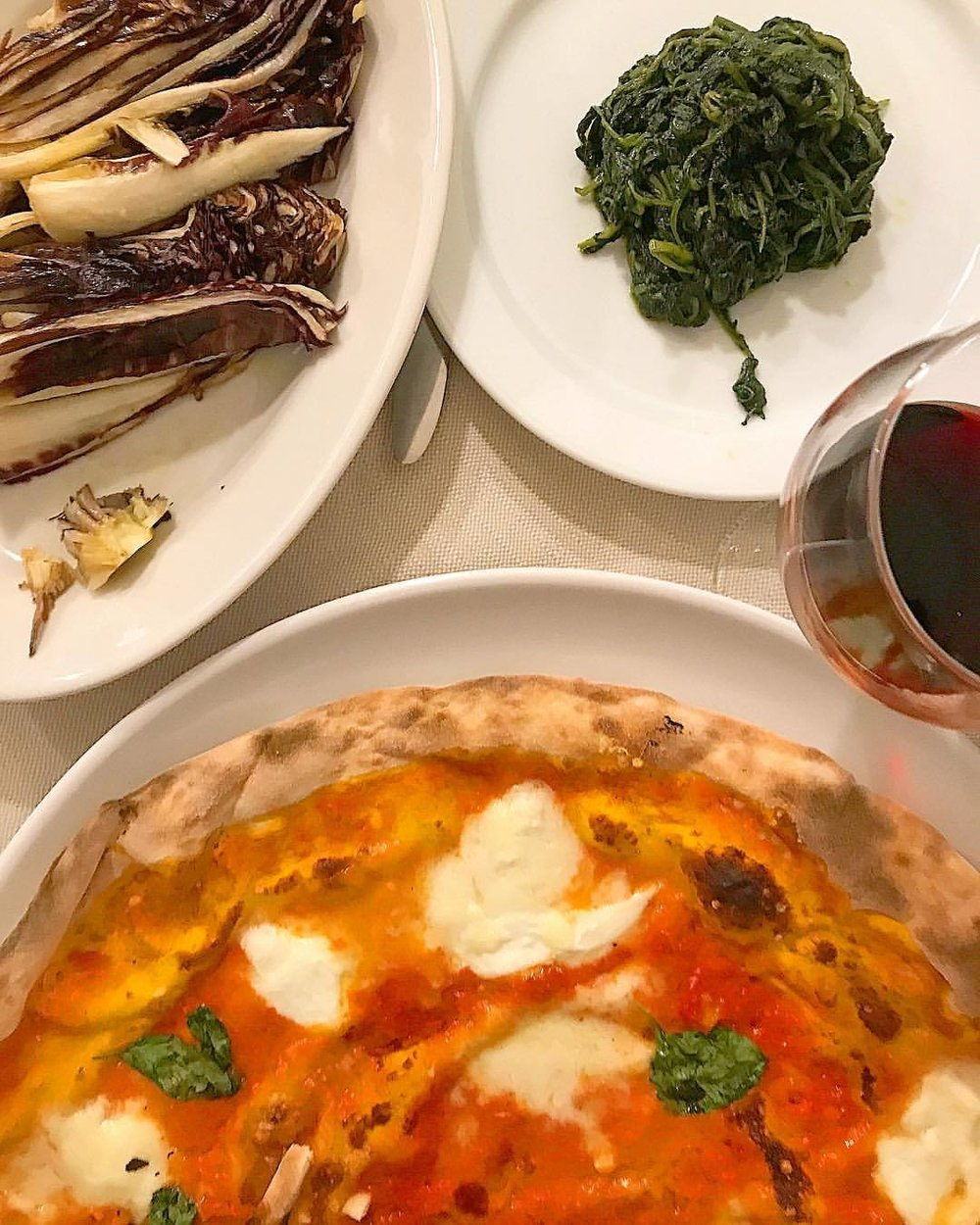 Ultra-thin crust Margherita pie with dreamy globs of buffalo mozzarella, grilled radicchio brushed with good oil, steamed chicories with fresh spicy garlic, and a bottle of better-than-it-has-to-be, local Sangiovese.  -  #italy #tuscany #trattoria #pizza #garlicisamiracledrug (at Ristorante Pinocchio Frascati Roma)