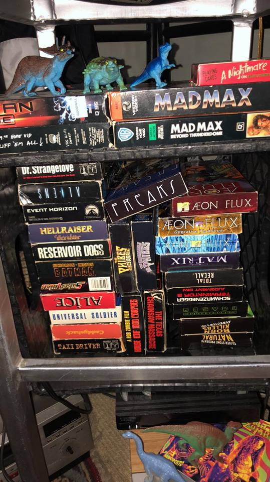 """COLLECTING VHS DOES NOT MAKE A HIPSTER! - by Mike WilcoxWhy do I collect antiquated media formats, aka why do I buy Trash?My friends call me a hipster. Technically they aren't wrong, but I would be lying if I said that I accepted and honored the title with no bitterness. The truth of the matter is that hipsters would be quite jealous of the communities that I frequent. While I still remain reasonably closer to the outer rims, friends of mine, accounts that I follow, folks that I interact with might as well still live in the 80's and 90's. Accounts like @theWallofVhs and @TheBetamaxRundown and @VCRofDeath (instagram) that post daily doses of old school b-horror and action and cult classic vhs films that a great many of us would often see on a weekend trip to Blockbuster Video. I live in the forgotten times. Typically you can find VHS tapes if not in a """"FREE: TAKE MY JUNK!!"""" pile, certainly for bargain basement listings. I usually pick mine up at my local record shops and haunts for around .25 cents a piece, maybe a bit more if it's a complete collection (like the rad 007 James Bond collection that I foolishly passed up not too long ago.) But aside from the nostalgia I am frequently asked the fateful question, """"Why do you collect junk?"""" When there are many higher quality formats available currently (I actually don't even own a blu-ray player, though it's been on my To-Get list for a bit now) why would I willingly spend money of any amount on these practically forgotten relics of an age and era forgotten? The simple answer is Aesthetics. The compound answer is culture and community. When I am viewing a film such as personal favorite, Tobe Hooper's 1974 Texas Chainsaw Massacre (or any of it's first four sequel films) there is some added quality to viewing it on VHS. The grainy picture quality. The occasional lines through the picture and warble of aged tape. The hype advertisement and graphics on the box. All of it add to the overall viewing experience. With a film of t"""
