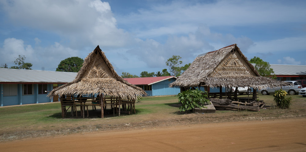 Adjacent high school with traditional structures built as gathering spots for the students.
