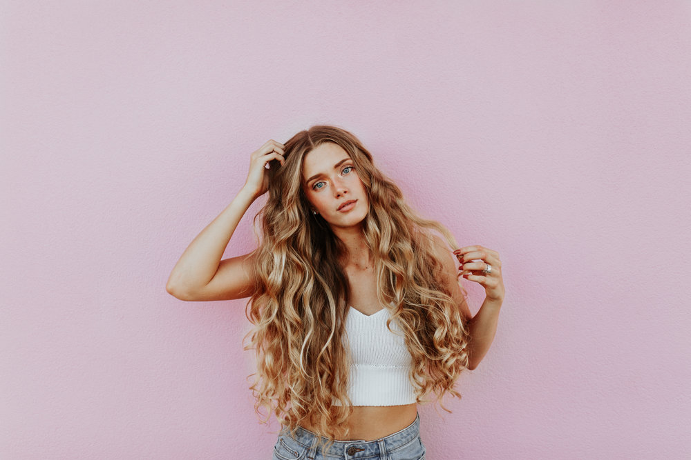girl with blonde hair on a pink background