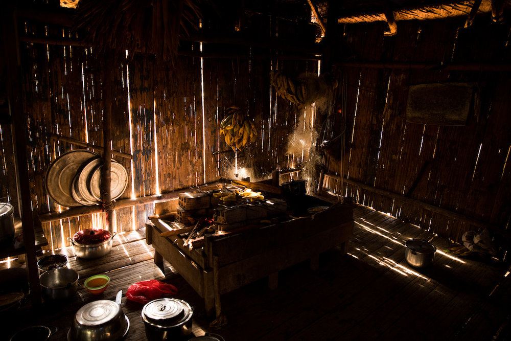 A typical Matsés kitchen - an open fireplace grilling plantain and manioc.