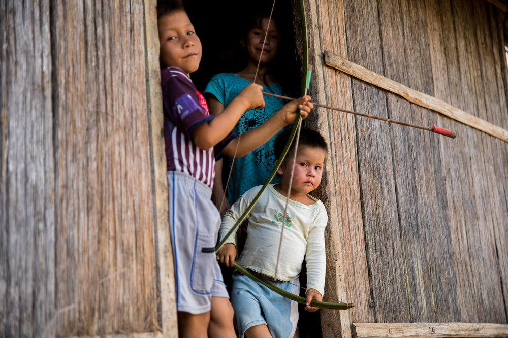 Children playing and practising with mini bow and arrows, a common sight in the villages.