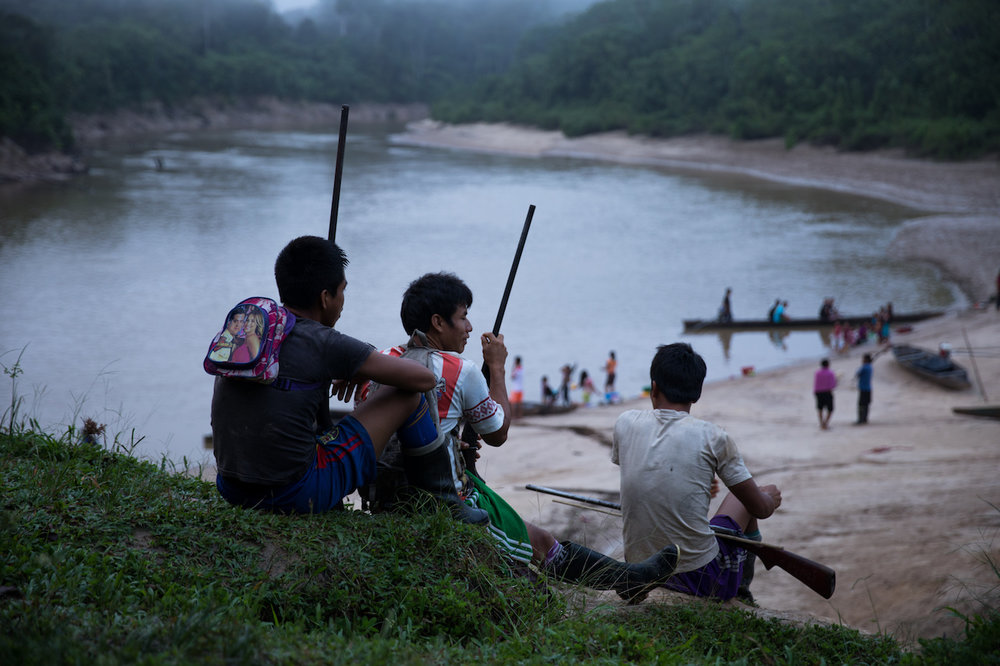 The modern hunters; Matsés youth preparing for a hunting expedition, shotguns, football tops and a pink bag.