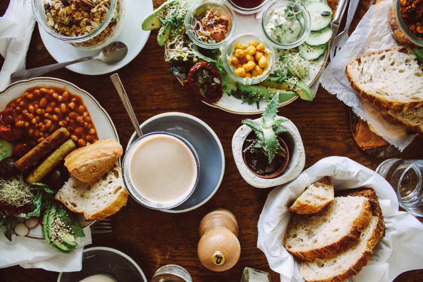 Different breakfast dishes at no58 speiserei Berlin. Johny Trader breakfast with baked beans, baked tomatoes, tofu sausages, stone mushrooms, avocado and sourdough bread; a bowl of yoghurt with granola a coffee as well as a plate with dips, chickpeas and avocado.