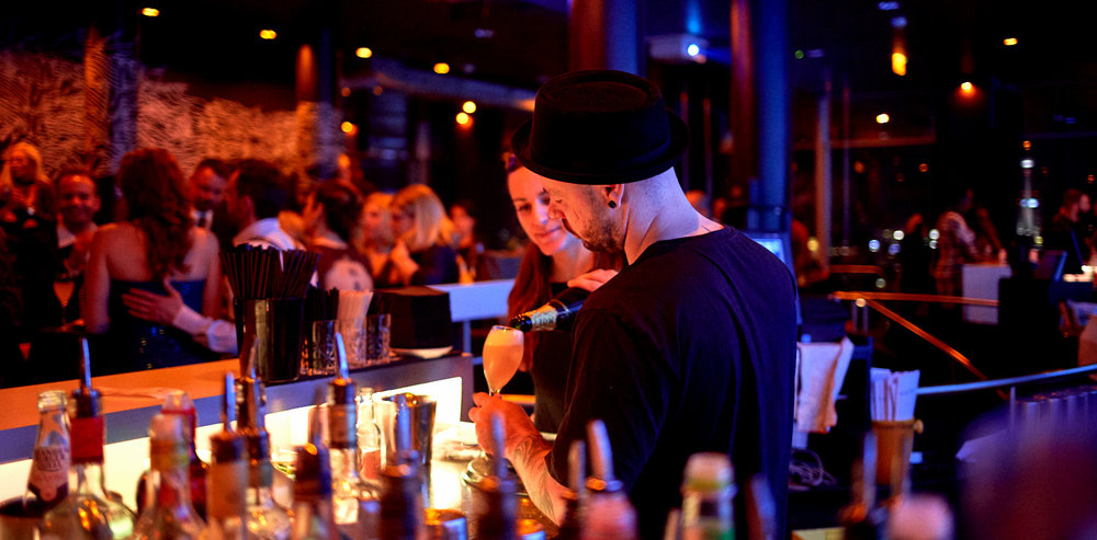 Bartender pouring champagne into a glass at Solar Skybar Berlin while a group of people is having drinks in the background with a view of the Berlin TV tower