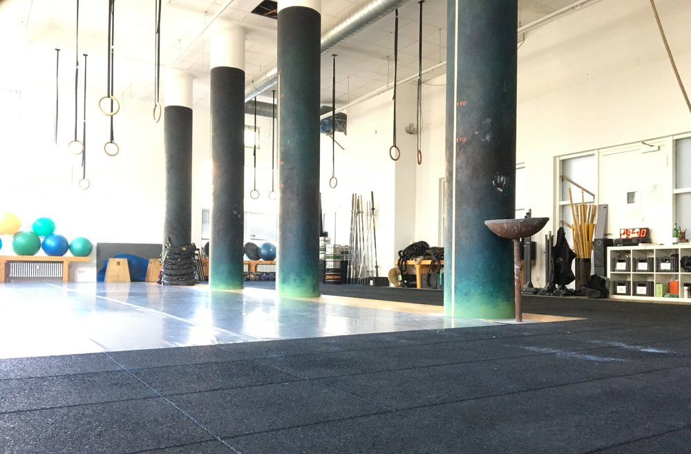 Workout studio at Urban Gladiators Berlin with rings hanging from ceiling, gymnastic balls on the side of the room and other workout equipment.