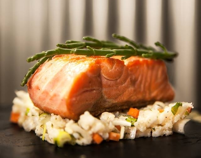 Salmon fillet on bed of rice with vegetables at Bar Raval Berlin