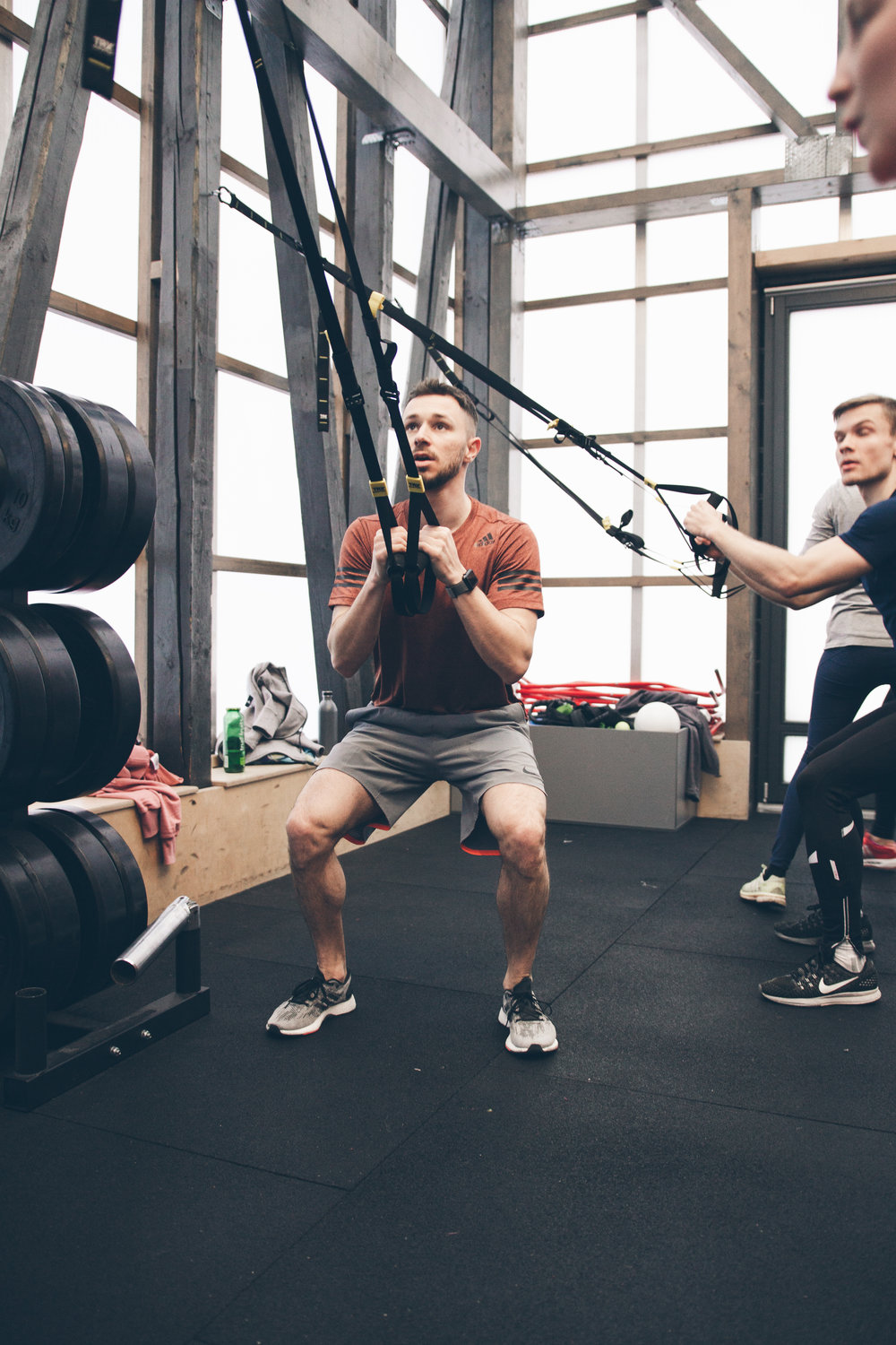 Guy squatting with TRX straps in hand and weights built up next to him at adidas runbase Berlin