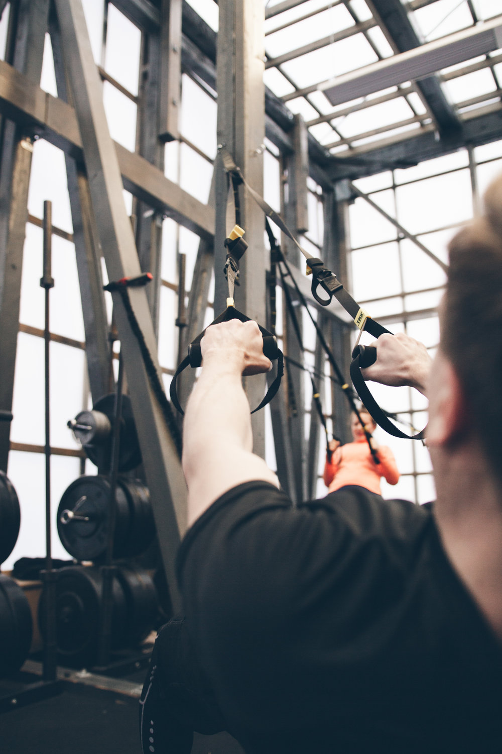 Girls and guys holding on to TRX straps pulling themselves up at adidas runbase Berlin