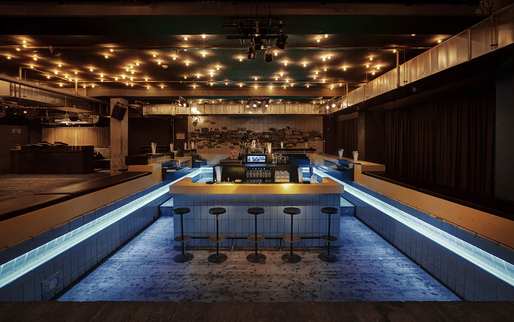 INdoor view of Prince Charles Club Berlin with a bar in the middle of a former swimming pool and lights at the ceiling