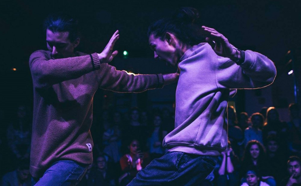 Couple dancing at Motions House dance studio in a room with dimmed lights