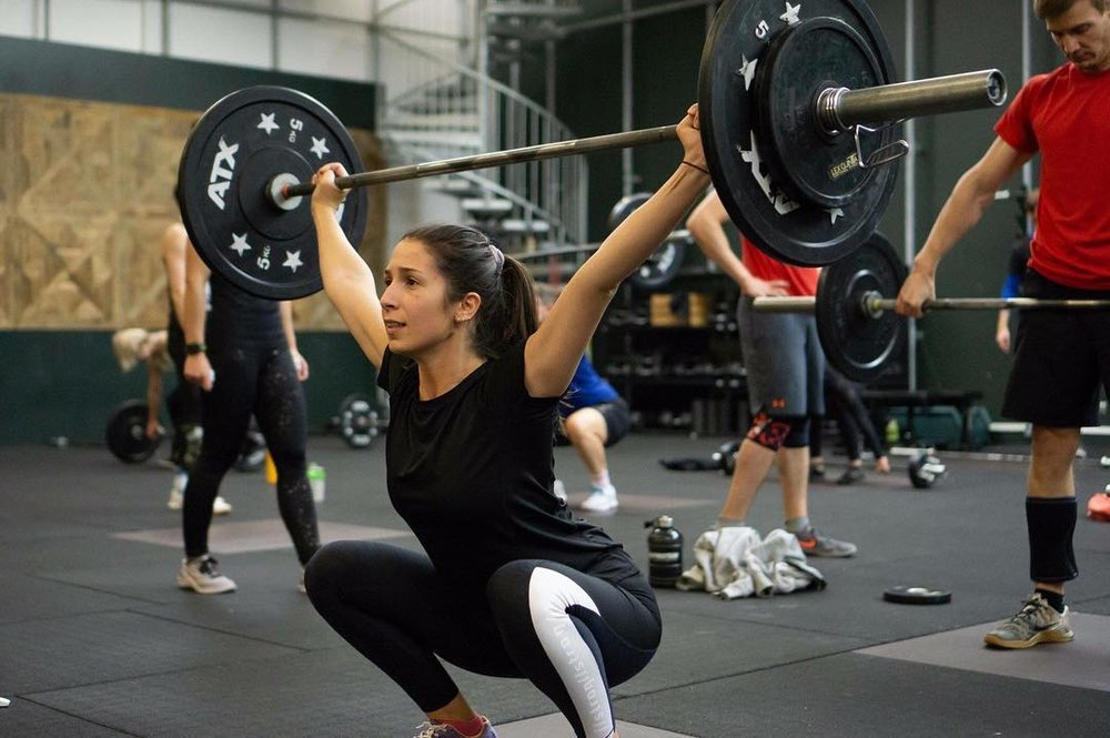 Girl in low squat with heavy weights at Crossfit Grenzgänger