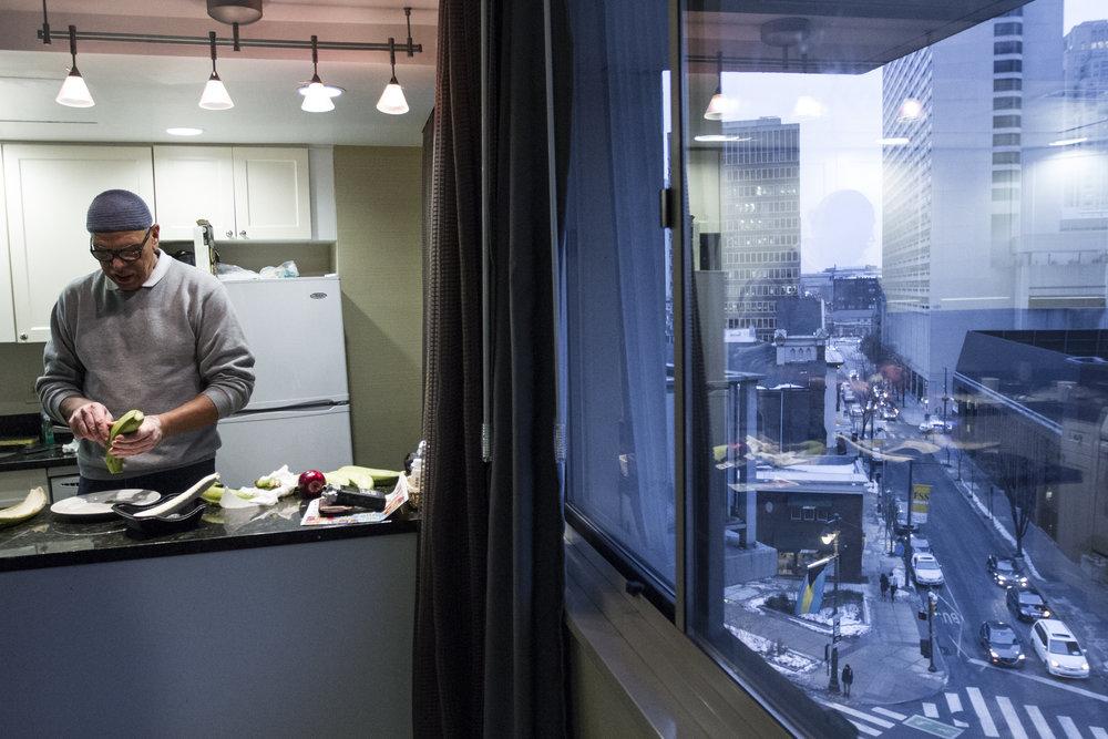 Raul prepares plantanos in a FEMA-sponsored hotel room overlooking the Benjamin Franklin Parkway in Philadelphia, Pennsylvania