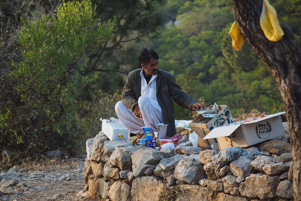 A vendor sells snacks and water for thirsty hikers