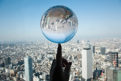 Glass globe balancing on finger with a city skyline in the background