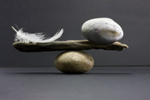 A stick with a rock and a feather one each side balancing on a rock