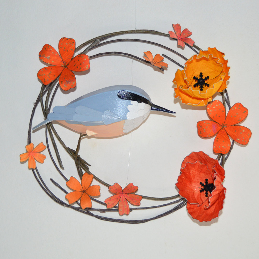 Stevie the nuthatch on a hoop of orange flowers