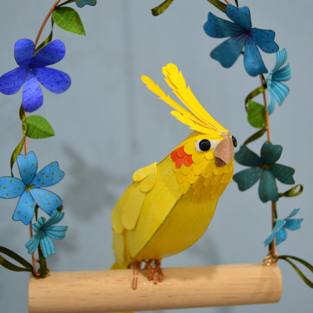 Happy the cockatiel on a swing with blue flowers