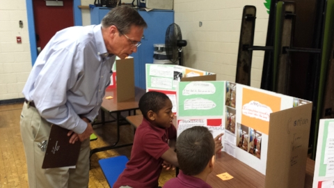 Mike Jones, NEP's Chief financial officer, judges a student's project at Hamilton STEM's annual science fair.