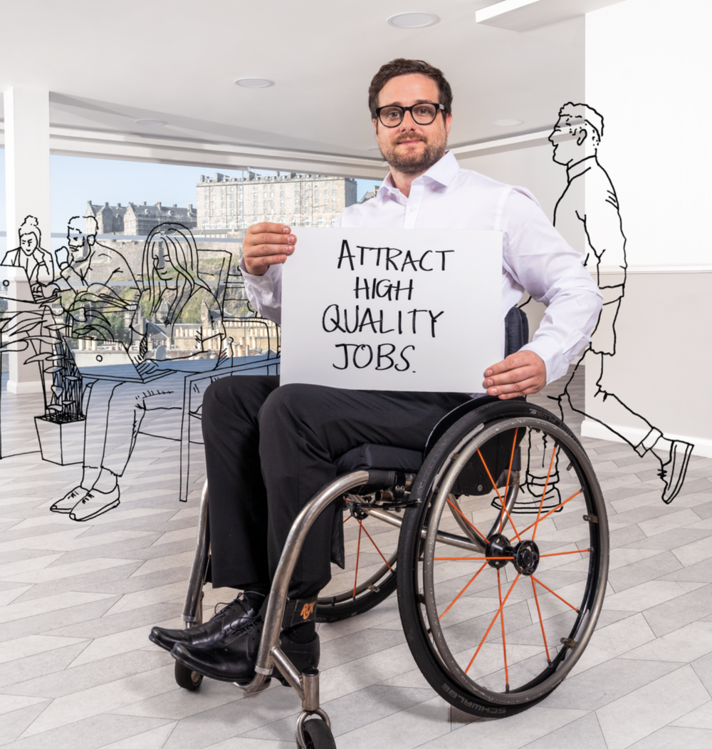 Man in an office holding a card saying 'attract high quality jobs'