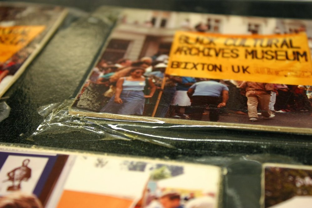 Detail of self-adhesive laminate and photographs adhered to boards.