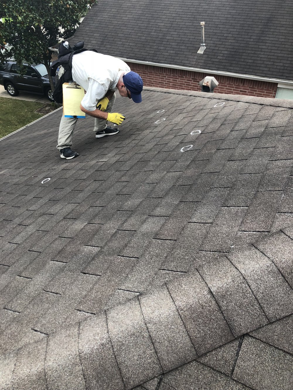 Our Team actively on a roof with an insurance adjuster assisting with a full roof replacement for hail damage..