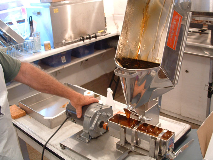 "The cooled syrup pours out of the ""pig"" shaped pan into the candy machine."