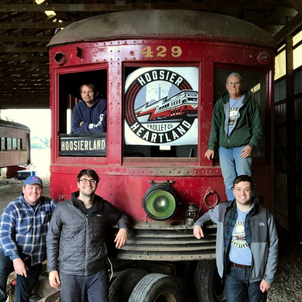 "Members of the Hoosier Heartland Trolley Company Board of Directors stand next to the recently relocated Indiana Union Traction Company Interurban No. 429 ""Noblesville"" - a vintage electric train car built in 1925 in St. Louis."