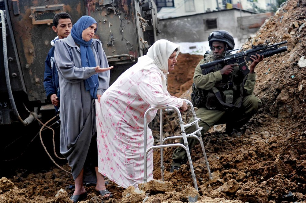 A Palestinian woman with her daughter, grandson and an Israeli soldier during a military operation / Gaza Strip 2005