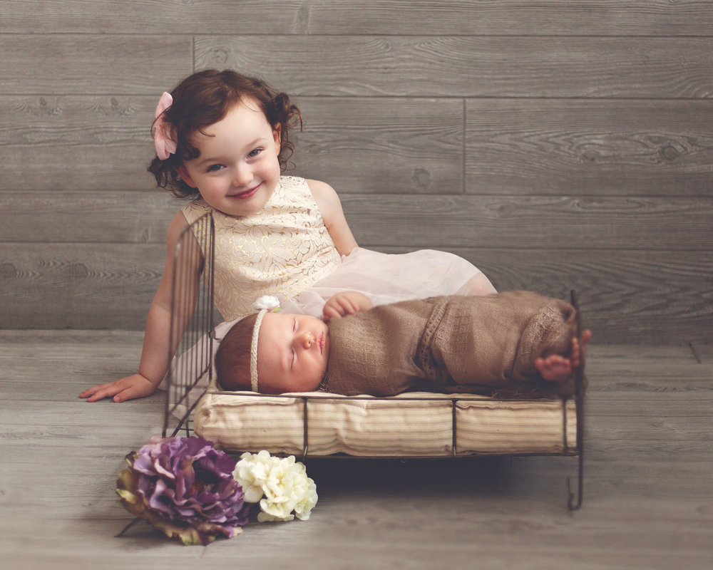 family photography of a newborn baby with her big sister