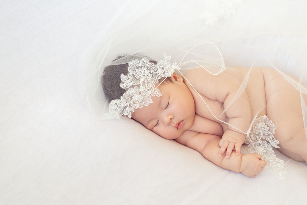 professional newborn photography of a baby with her mothers wedding veil