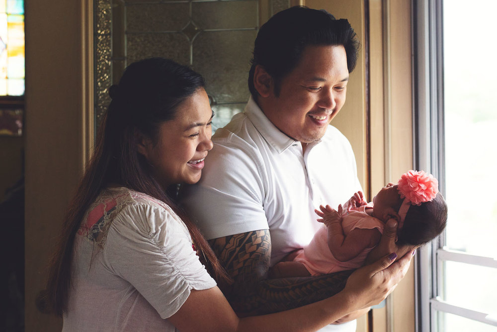 newborn lifestyle photograph of parents holding their baby girl in belleville new jersey
