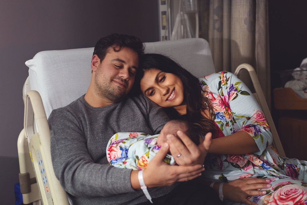Fresh 48 Photography of newborn baby girl with mom and dad in hospital bed in Mountainside Hospital in Montclair New Jersey