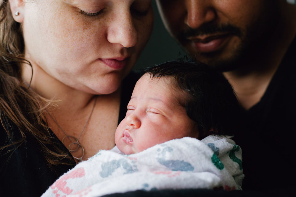 Fresh 48 Photography of newborn baby girl in mom and dads arms in Hackensack Hospital in Hackensack New Jersey
