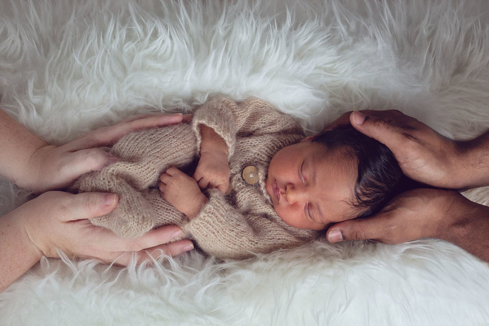 artistic newborn photograph of a baby in mom and dads hands in rutherford new jersey