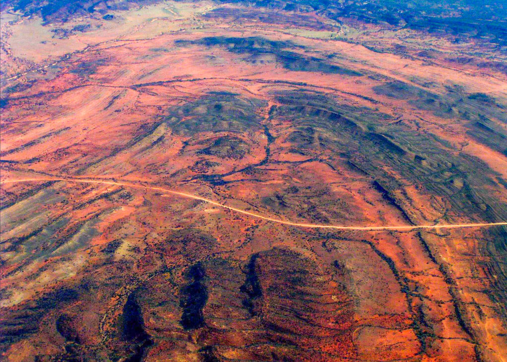 Mesmerising curved patterns of the Simpson Desert in Queensland, as seen from above. They are visual expression of folded planar surfaces of rock layers intersecting the Earth's surface. Image:  Dietmar Müller via Flickr .