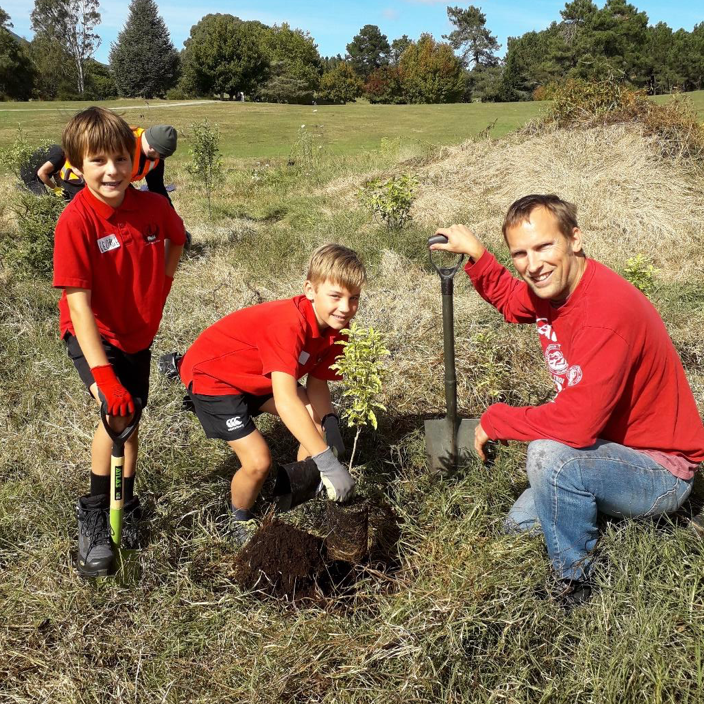 Students from Taupo Primary work alongside of Cheal Consultants staff member, planting natives at Spa Park as part of a company community service project.