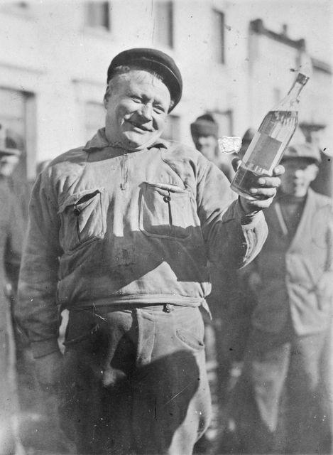 Kieltolain päättymisen tunnelmia vuodelta 1932. Koko yön jonottanut Iisalmen viinakaupan ensimmäinen asiakas esittelee saamaansa ilmaista pulloa. Kuva Kimy-Kustannus / Museovirasto, Historian kuvakokoelma.