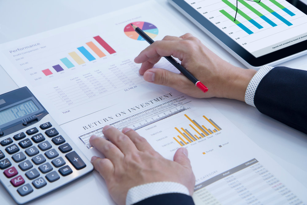 Investments graphs calculator and mans hands holding pen.jpg
