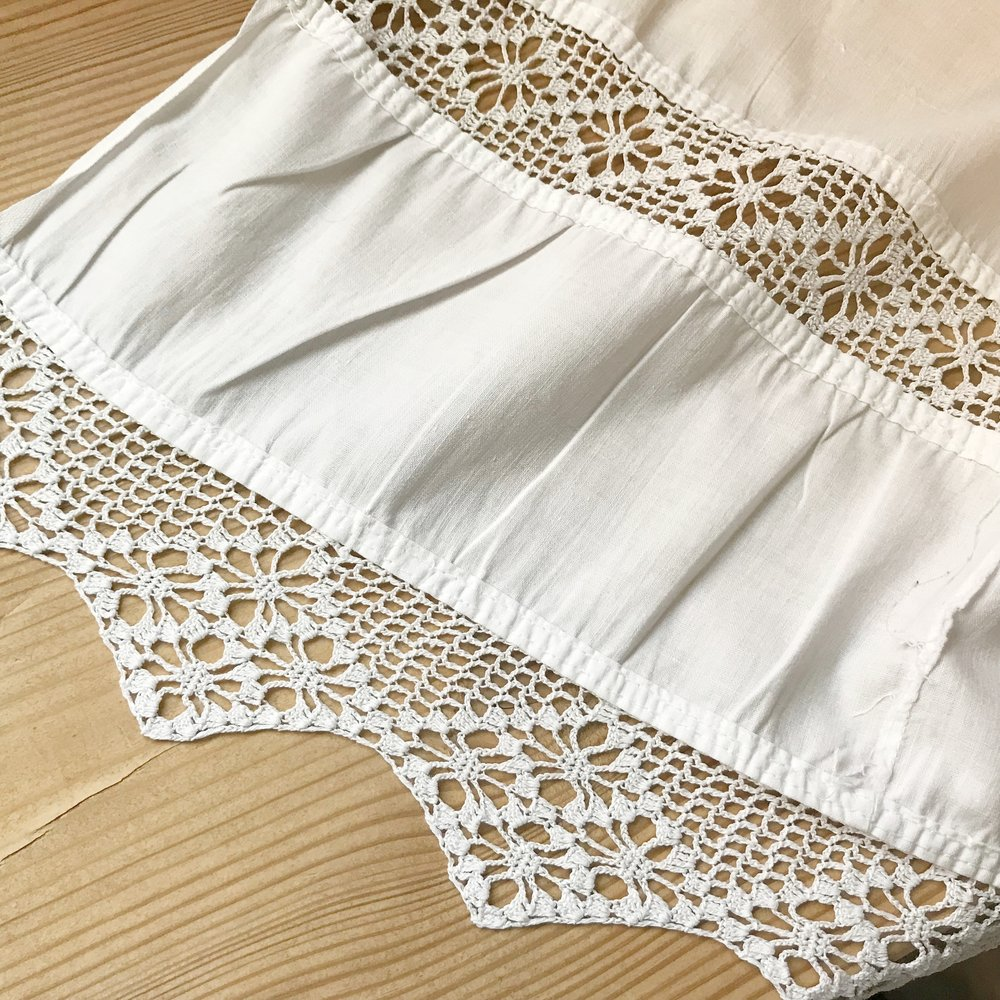 This sheet has two rows of hand-made lace -- one row inset into the sheet. The sheet had obviously been remade at one point -- perhaps the lace parts had been removed from one sheet and hand-stitched to this one.
