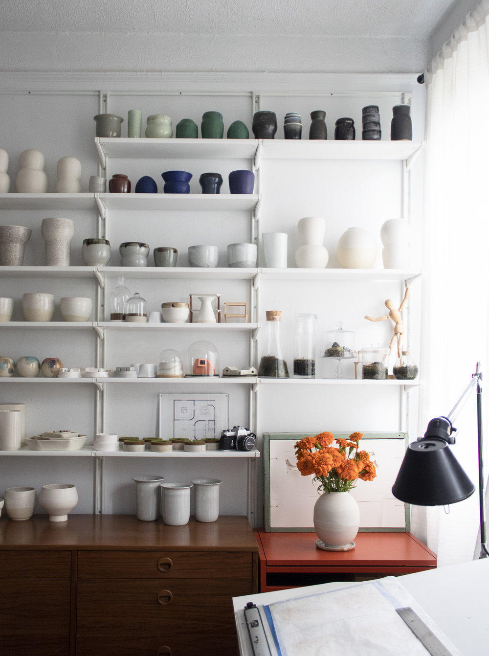 Leticia and Jason's constantly growing collection of ceramics and architectural models is displayed in their bedroom.