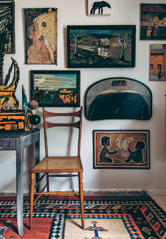 A Giuseppe Romeo sculpture elevates a gallery wall of outsider artworks behind it.