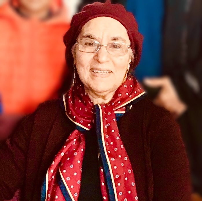 Image of Habibe Husain, she is wearing a red sweater, red scarf, and red hat. She is seated with people blurred behind her.