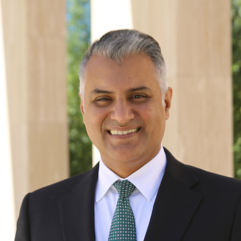 Image of Omair, there are wooden pillars and greenery behind him. He is wearing a suit with a green tie and smiling.