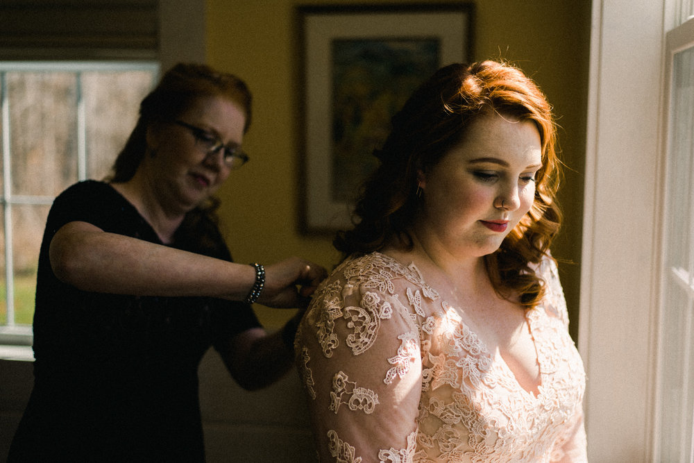 mother helping bride dress
