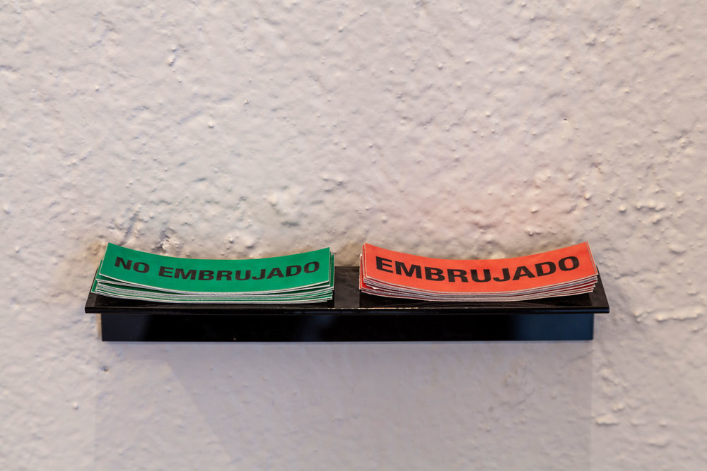 Anthony Discenza (New Jersey, 1967),  Embrujado / No embrujado , 2018. Two reflective vinyl stickers, 7.62 x 2.54 cm each