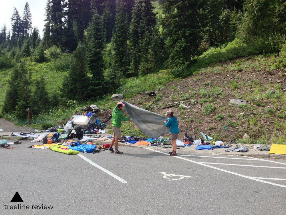 Drying out and folding a tent in a parking lot.   Photo by John Carr