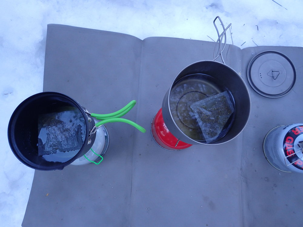 We went through a lot of canisters in the testing of these stoves. This is a photo of a side-by-side comparison test in the snow. Yes, we know that the comparison of speed and efficiency can't truly be measured using different pots and different canisters. Instead, we are testing ease of use.   Photo by Liz Thomas.