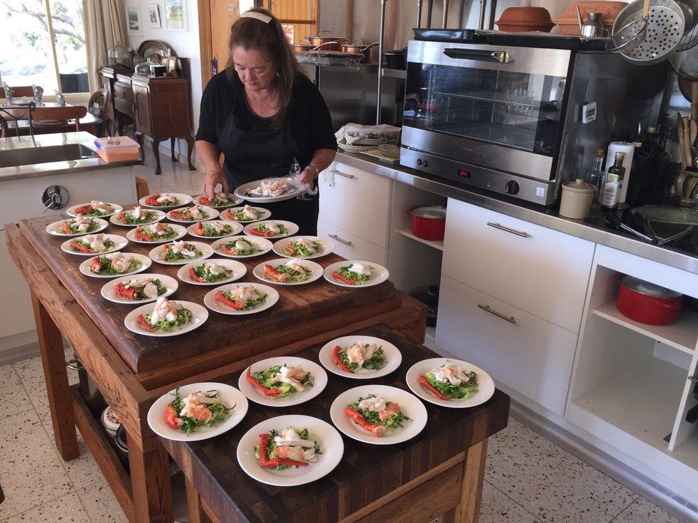 Plating up a crayfish salad on a chiffonade of fresh-from-the garden greens for a long table lunch.
