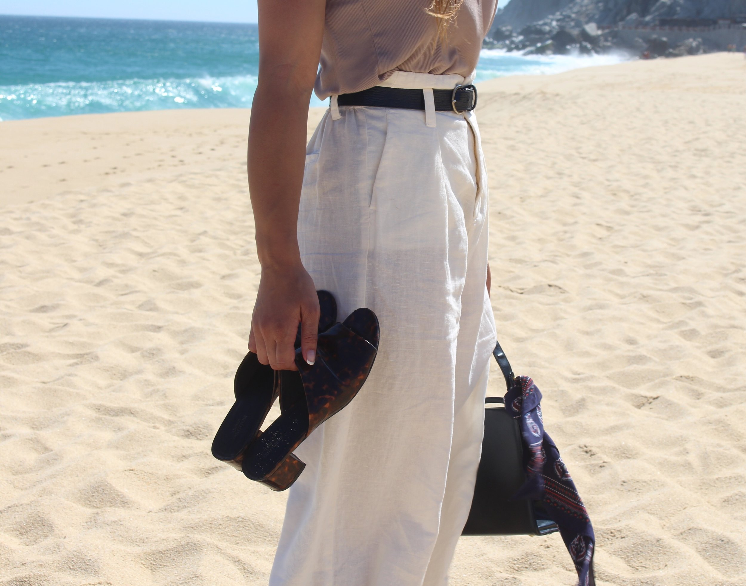 Woman wearing white pants and holding sandals on the beach in Cabo San Lucas Mexico.